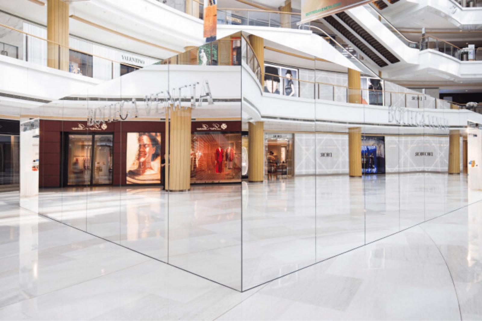 """Shanghai: Bottega Veneta crea """"Lo Store Invisibile"""". In una piazza di un centro commerciale di Shangai, il concept store di Bottega Veneta è racchiuso in un grande quadrato con degli specchi all'esterno che, voltontariamente, riflettono i loghi dei negozi dei competitors come Dior e Valentino. Fonte immagine: Luxus Plus"""